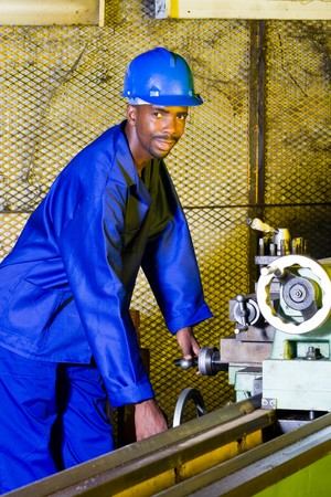 African machinist operating a lathe machine photo