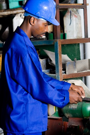 African machinist operating a grinding machine photo