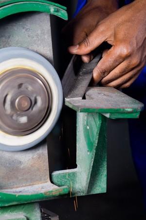 closeup of a machinist operating a grinding machine photo