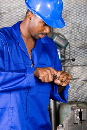 african machinist filing on metal material photo