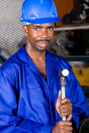 african machinist standing with a hammer photo
