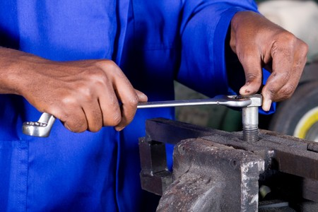 closeup of man with spanner working on machine part photo