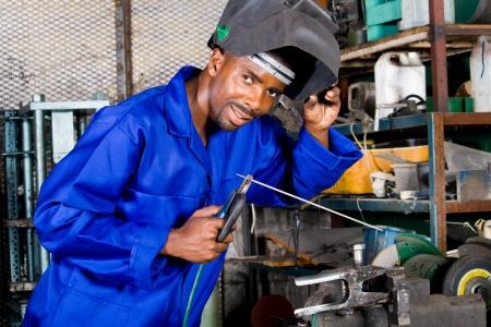 welding metal: african male welder with welding equipment Stock Photo