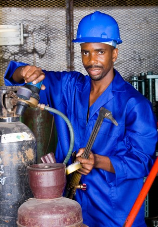 african male welder with protective gear and gas welding machine photo