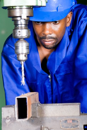 african male machinist working on industrial drilling machine