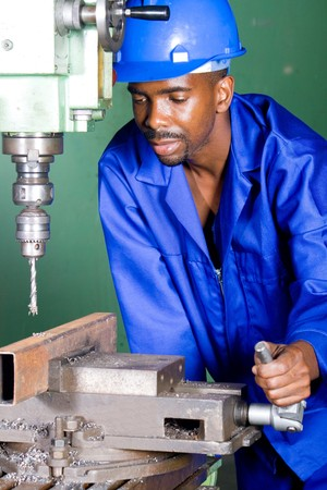 african male machinist working on industrial drilling machine Stock Photo - 4255876