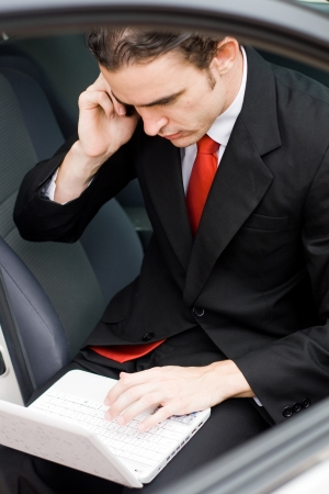 young caucasian businessman working on laptop and cellphone inside a car photo