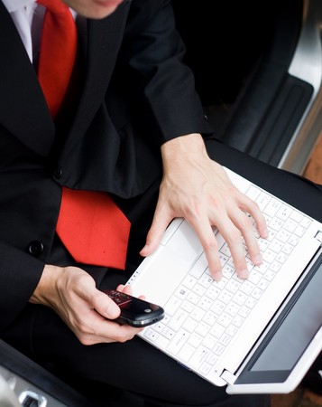 young businessman sitting inside a car and working on laptop photo