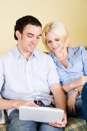 outworking: Couple browsing internet on laptop at home Stock Photo