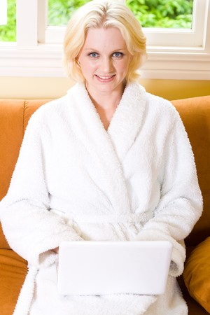 young happy woman using laptop in bathrobe photo