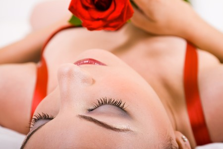 glamor woman with rose in bed photo