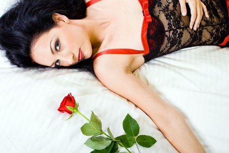y glamor woman in lingerie holding rose in bed Stock Photo - 4419213