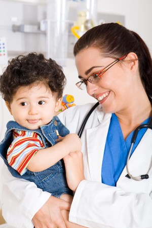 young smiling female pediatrician holding a cute baby boy     photo