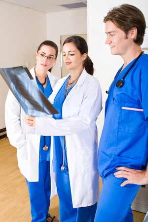three doctors looking at patients x-ray film photo