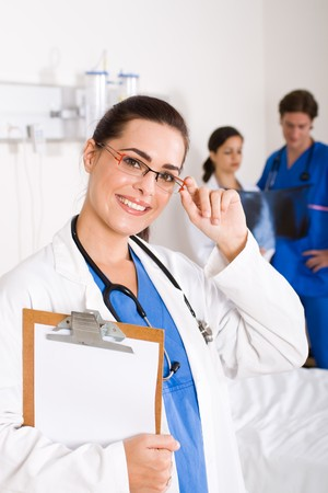 smiling female beautiful doctor in hospital, background is her colleagues photo