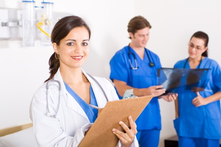 smiling female beautiful doctor in hospital, background is her colleagues Stock Photo - 4411340