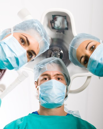 Team of medical professionals looking down at patient in surgical theater