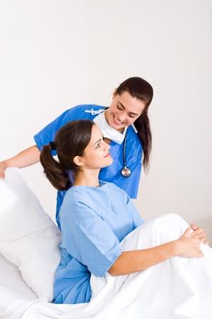 friendly nurse helping female patient in hospital ward photo