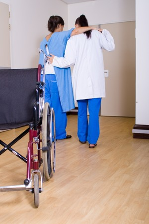 hospitalization: doctor or nurse helping her patient to walk without wheelchair Stock Photo