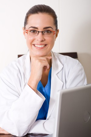 young female doctor sitting by her laptop computer photo
