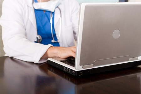 stethescope: doctor using laptop doing work
