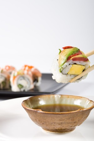 sushi roll dipping in soy sauce photo