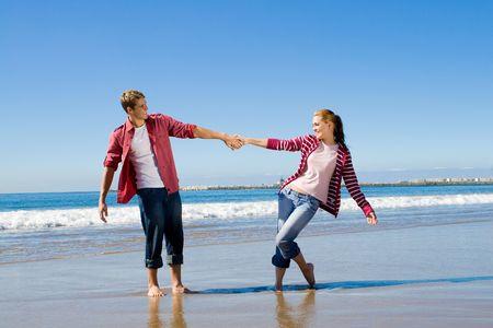 horsing around: couple playing on beach