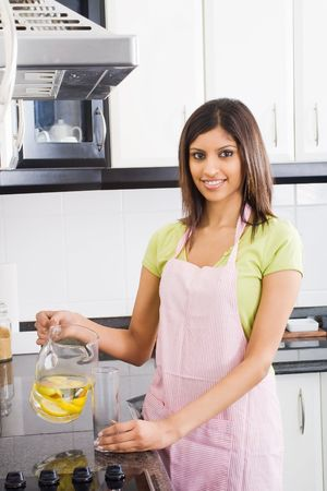 young attractive woman pouring drinks in kitchen Stock Photo - 5493071