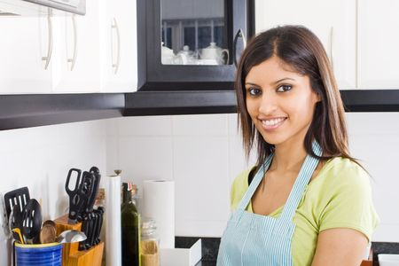 indian cooking: young housewife in kitchen with apron