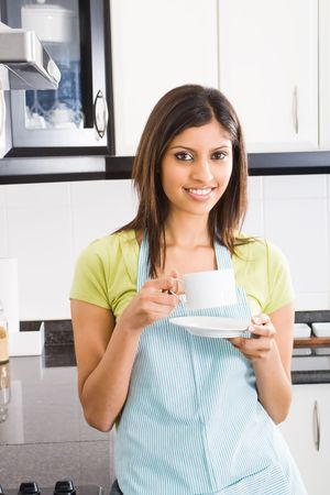 kitchen ware: young happy attractive girl drinking coffee in kitchen