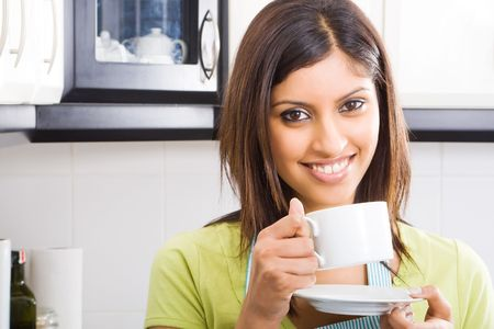 ware house: young happy attractive woman drinking coffee in kitchen