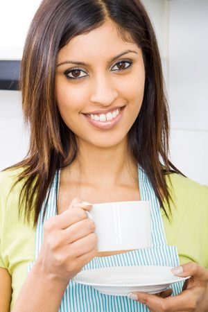 young happy attractive woman drinking coffee in kitchen photo