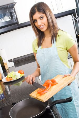 asian flavors: beautiful young woman cooking in kitchen Stock Photo