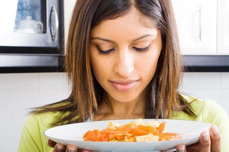 olfato: la mujer que huele la comida caliente en la cocina