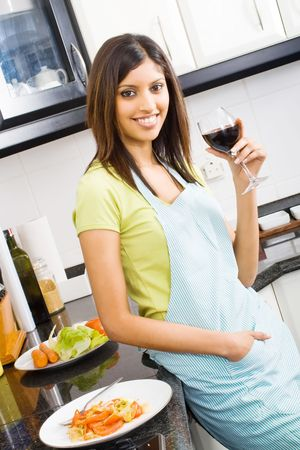 indian cooking: young woman drinking and eating in kitchen