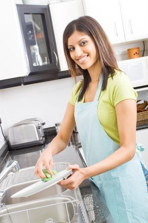 young woman washing dishes in kitchen Stock Photo - 5493163