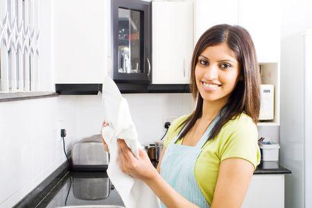 ama de llaves: mujer joven secar los platos en la cocina