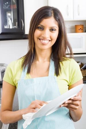 lavare piatti: giovane donna di essiccazione i piatti in cucina