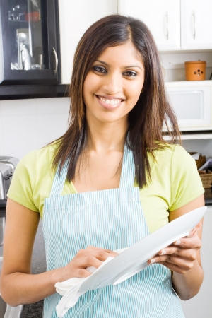 young woman drying dishes in kitchen Stock Photo - 5493070
