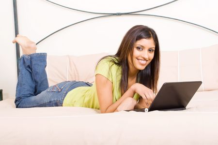 young arabian woman relaxing on bed with laptop photo