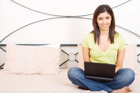 young woman using laptop computer on bed at home photo