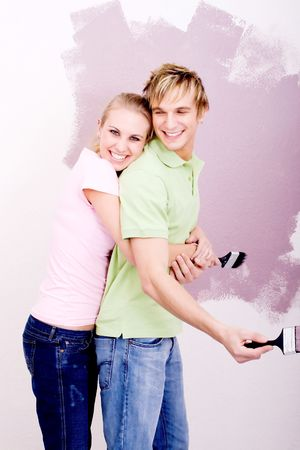 young couple painting new home photo