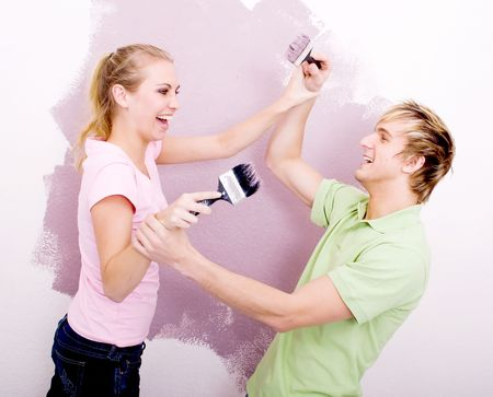decorate: couple having fun while painting house Stock Photo