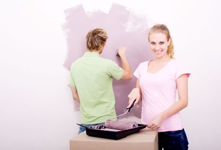young couple painting house photo