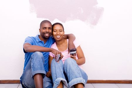 redecorating: happy africa couple painting home Stock Photo