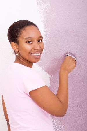 african woman painting wall photo