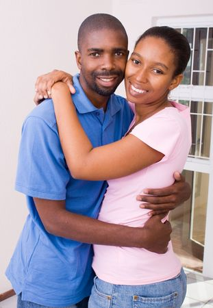 african couple hugging in empty new home photo