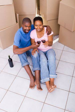alcohol cardboard: african american couple celebrating first new home