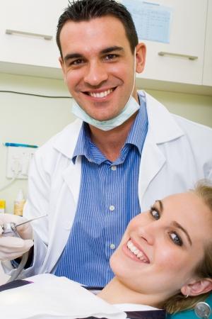 uniformes de oficina: feliz dentista y el paciente en el consultorio del dentista