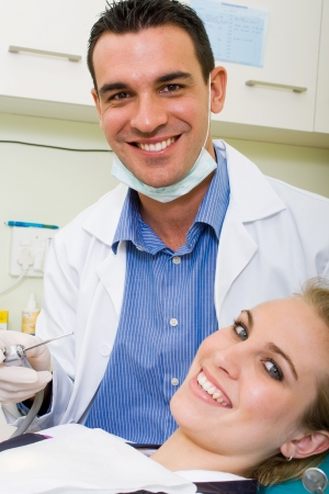 happy dentist and patient in dentists office photo